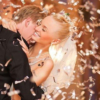 Wedding couple surounded by glittering gold confetti for first dance